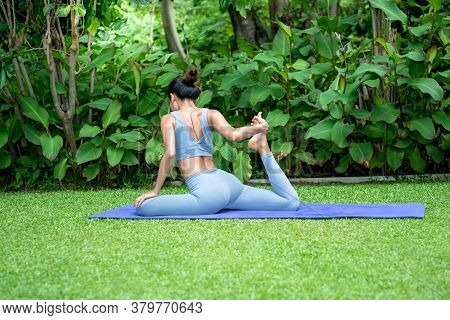 Asian Attractive Young Woman Have A Beautiful Body, Doing Yoga In An Elegant Posture, In The Green P