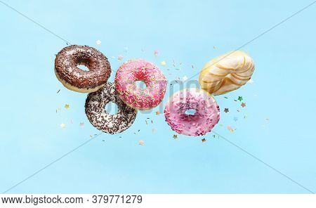 Glazed Doughnuts With Sprinkles Flying Over Blue Background.