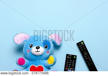 Black Tv Audio Remote Control And Baby Toys Rattles, Toy Puppy On Blue Background Flat Lay Top View