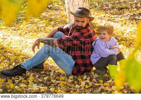 Happy Father And Son Sitting On Fallen Yellow Autumn Leaves. Active Men Family Time On Nature