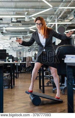 A Woman In A Suit Is Engaged On A Rocker-skateboard During A Break At Work. A Female Office Employee