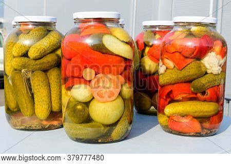 Three Jars With Mixed Pickles On A White Table For Sale At A Food Market With Pickled Cucumbers, Gre