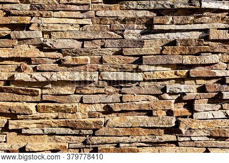 Background Wall Of Stones. The Surface Of The Stones Is Brown. Background Texture. Masonry Of Thin V