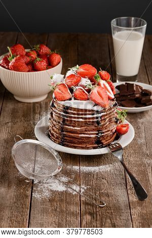 Hot Brown Pancakes Adorned With Strawberries, Chocolate And Icing Sugar