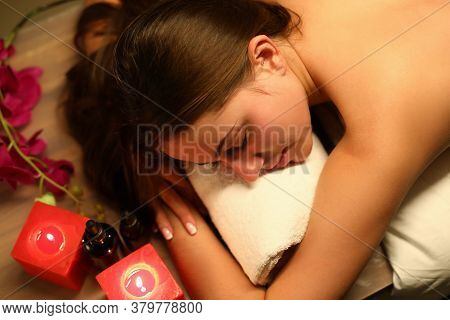 Top View Of Glad Smiling Young Woman Laying In Spa Salon. Bottles With Aromatic Oils On Table And Ca