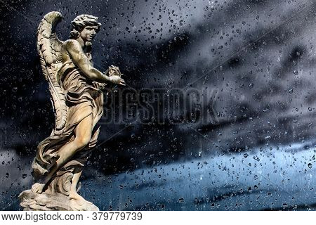 Statue Of A Monument To An Angel On A Background Windows With Raindrops And Dramatic Dark Sky.