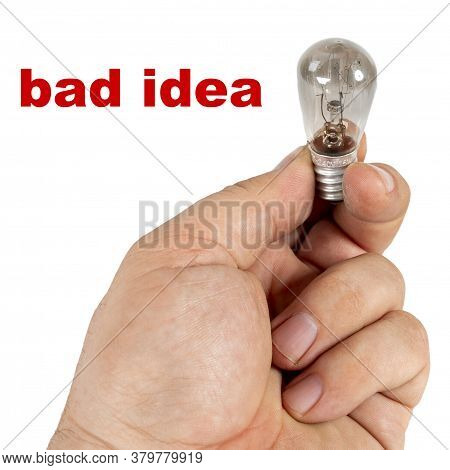 Bad Idea. A Hand Holds An Old Blown Incandescent Lamp. Isolated On White Background And The Inscript