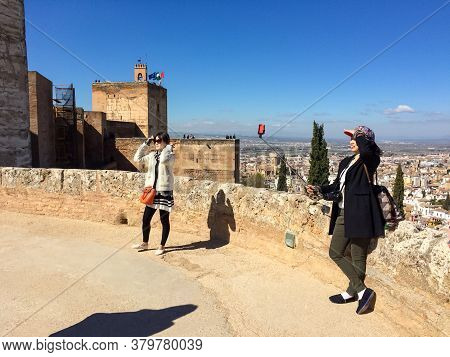 Granada, Andalusia / Spain - March 27: Two Asiatic Women Taking Pictures With Her Smartphones In A B