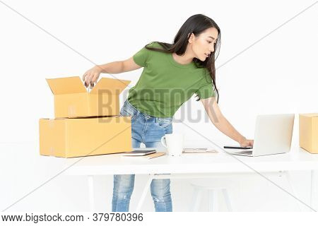 Young Asian Casual Woman Working Small Business Online Packing Product To Cardboard Box.startup Smal