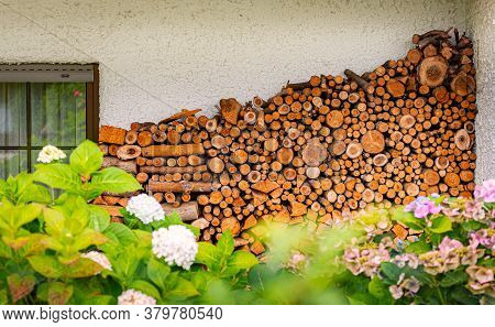 Stack Of Wood Logs. Preparation Of Firewood For The Winter. Pile Of Chopped Lumber Near House In Bav