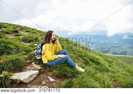 A Hiker Woman Is Talking On The Smartphone While Sitting On The Top Of The Mountain. Backpacker Girl