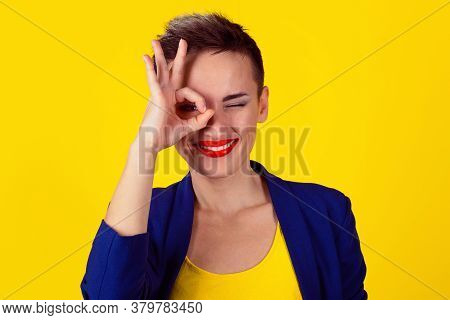 Woman With Her Fingers Over One Eye, Ok Sign Hand Gesture Isolated On Yellow Background. Model In Ye