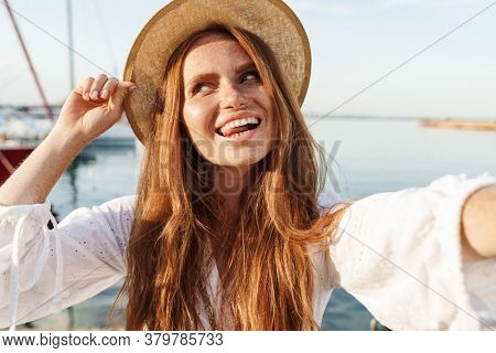 Image of cheerful woman showing tongue and taking selfie photo while walking on promenade