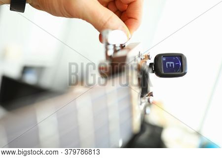 Close-up Of Tuner And Hands Of Musician Tuning String Instrument. Man Using Special Device For Elect