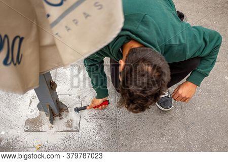 Jerez De La Frontera, Cadiz / Spain - April 8 2015: Man Using A Green Sweater, Holds A Wrench To Tig