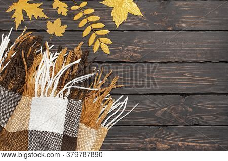 Woolen Checkered Plaid. Autumn Background. Checkered Yellow Brown Plaid With Golden Leaves On Dark W
