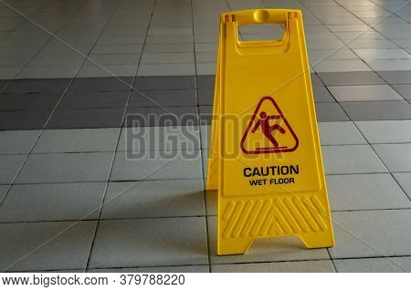 Wet Cleaning Of The Room On The Wet Tile Floor Is A Yellow Stand With The Inscription