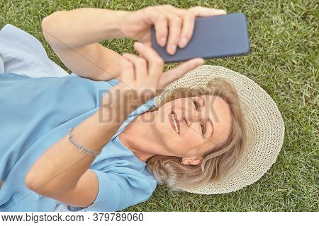 Elderly Pretty Caucasian Lady About 62 Years Old Is Lying Down The Grass Outdoor In Hat And With Sma