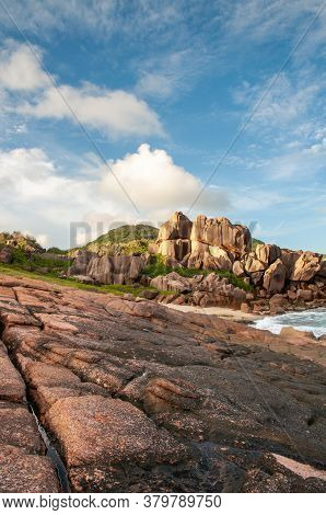 Rough And Wild Rocky Coastline At Anse Songe With Lush Green Grass, Tropical Vegetation, Red Granite