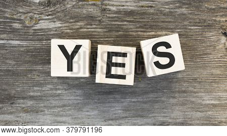 The Word Yes. Written In Black Letters On Wooden Blocks. Message Spells Yes On White Background. Bus