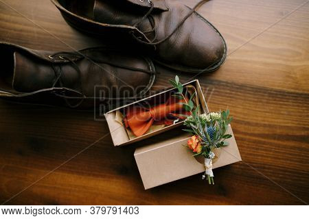 Close-up Of A Bow Tie For A Groom With A Boutonniere On A Cardboard Box And Mens Shoes On A Brown Fl