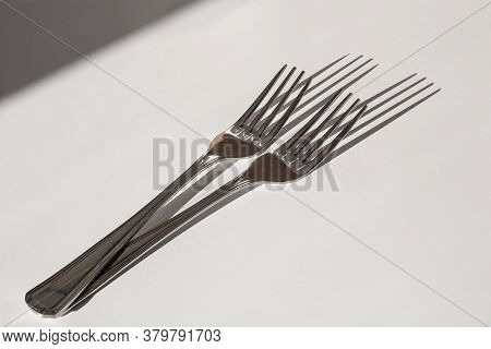 Two Elegant Stainless Forks On White Table With Sharp Sunny Shadow.