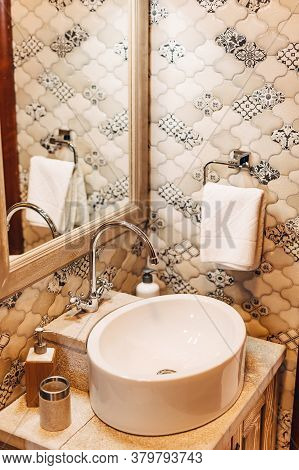 White Washbasin With A Large Mirror And A Towel Holder Against A Patterned Wall.