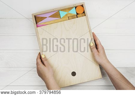 A Box Of Childrens Wooden Designer In His Hands. Wooden Constructor For Children. Colorful Toys Made