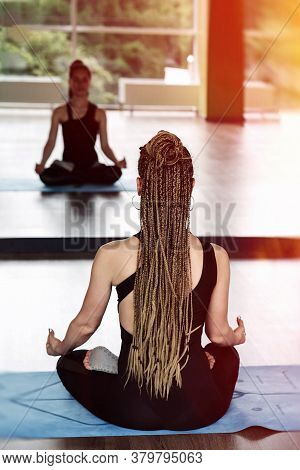 A Girl In A Black Jumpsuit With Afro Braids Sits In A Lotus Position With A Mudra Gesture And Medita