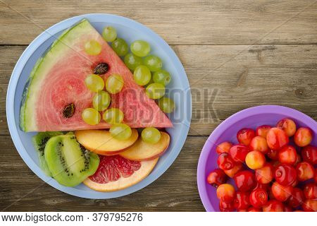Sliced Fruit On A Wooden Background. Sliced Fruit On A Light Blue Plate Top View.