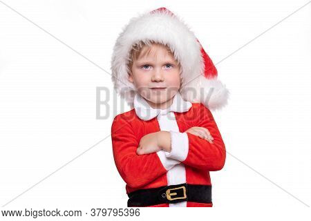 A Child Boy In A Red Suit And A Santa Claus Hat Stands With His Hands On His Chest. A Positive Story
