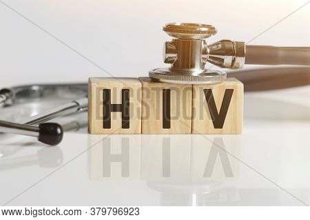 Hiv The Word On Wooden Cubes, Cubes Stand On A Reflective White Surface, On Cubes - A Stethoscope. M