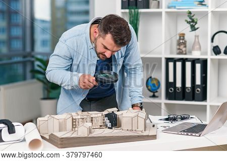 Architect Male Inspector Examines A House Model Using A Magnifying Glass. House Inspection And Real