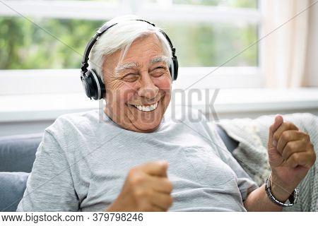 Smiling Older Senior Listening Music On Headphones