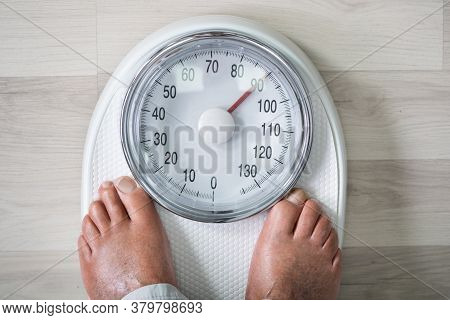 Man Feet On Weight Scale. Obesity And High Cholesterol