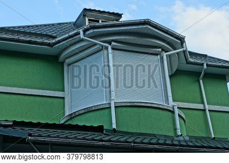 Balcony Closed With White Blinds In The Green Attic Of A Private House Against The Sky
