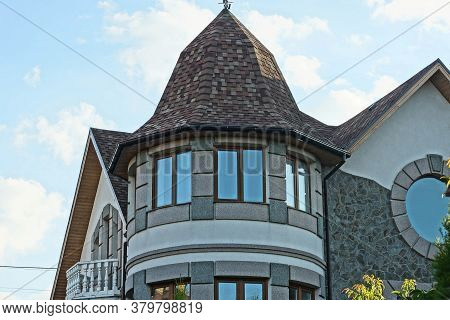 Brown Tower And Attic Of A Private House With Windows Under A Tiled Roof Against The Sky