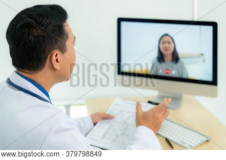 Asian Man Doctor Wears White Coat And Headset Speaking Videoconferencing On Laptop Computer Using On
