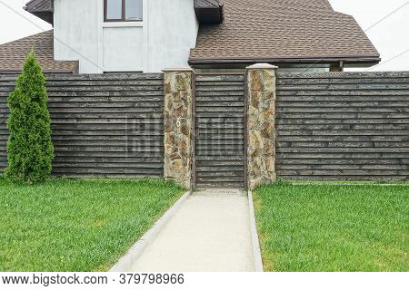 Gray Brown Closed Door And Wooden Fence Wall Outdoors In Green Grass And Coniferous Decorative Tree