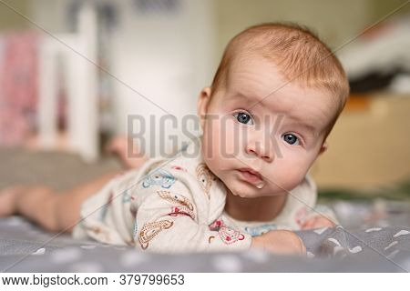 Newborn Baby Lies On His Stomach, Keeps His Head On Weight, Drooling, Droplets Are Visible On  Lips
