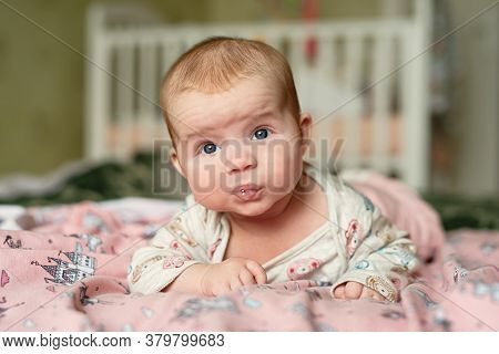 Small Child Lies On His Stomach, Drooling With Bubbles On  Lips, Girl Holds Her Head With Difficulty