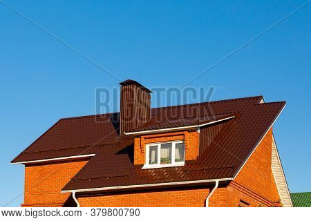 Roof Of A Brick House Or Cottage Made Of Brown Metal Tiles With A Bay Window, Gutters, Tides And A C