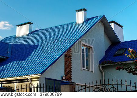 Roof Of A House Or Cottage Made Of Blue Metal Tiles With Drains, Slopes, Tides, Chimney Against The