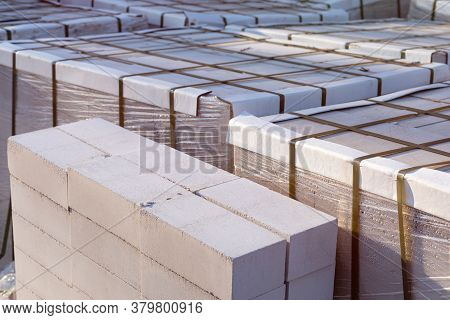 Silicate Brick On Wooden Pallets Wrapped In Transparent Plastic Wrap At A Construction Site