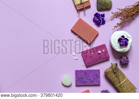 Layout Of Purple Eco Soap, Natural Pumice, Washcloth And Flowers . Top View On A Lilac Background Wi