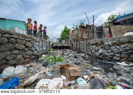 Santo Domingo / Dominican Republic - May 16 2018: Chidren Playing Near The Aqueduct Full Of Garbage