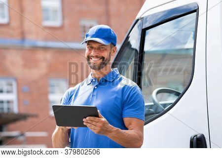 Delivery Man Near Truck Or Van Using Tablet