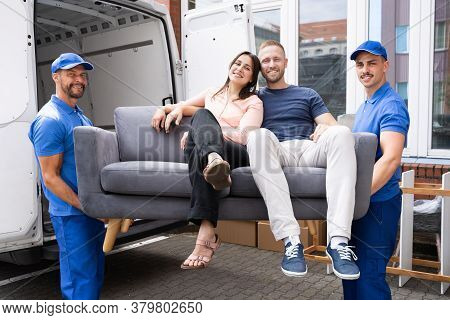 Two Male Happy Furniture Movers Carrying Couple Family On Sofa Out Of Truck