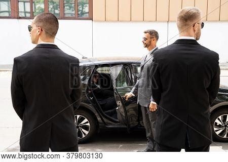 Bodyguards Protecting Businesswoman Opening Car Vehicle Door