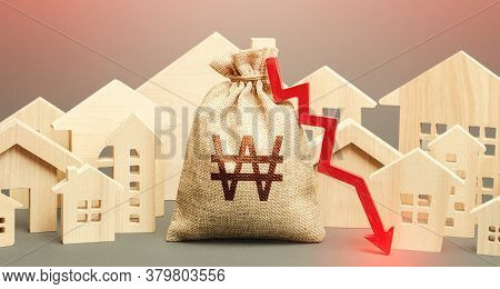 City Residential Buildings And South Korean Won Money Bag With A Red Down Arrow. Low Demand For Home